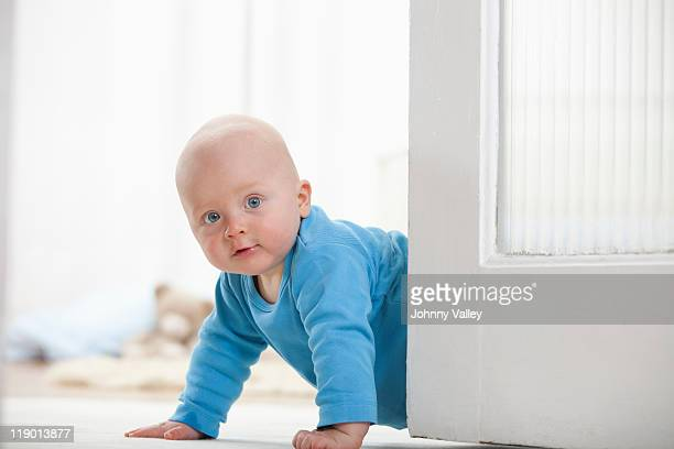 Baby boy crawling around door