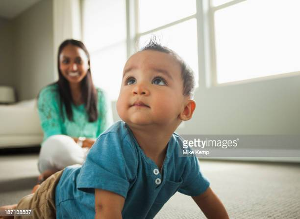 baby boy crawling in living room - indian baby stock photos and pictures
