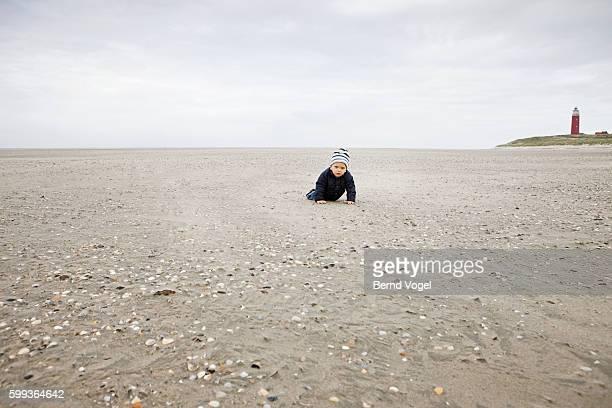 Baby boy crawling on beach