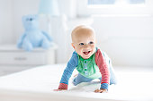 Baby boy crawling on bed