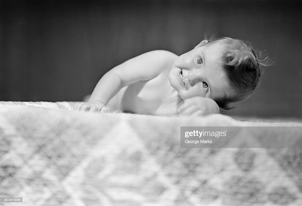 Baby boy (2-5 months) crawling on bed : Stock Photo