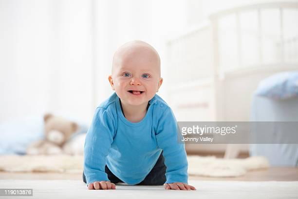 Baby boy crawling on carpet