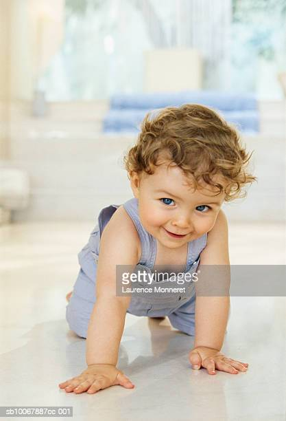 Baby boy (9-12 months) crawling on floor, smiling, portrait