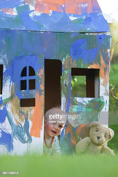Baby boy crawling out of cardboard house