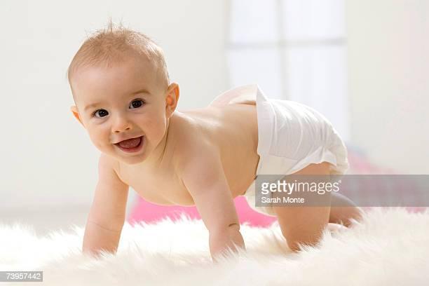 Baby boy (6-12 months) crawling, smiling, portrait