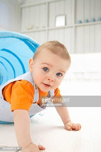 Baby boy (9-12 months) crawling through tube, portrait, close-up