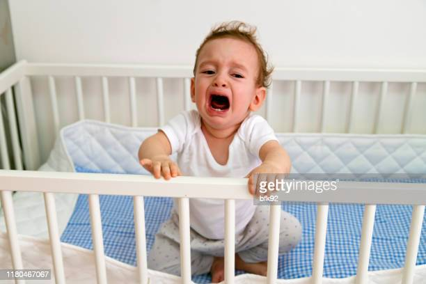 baby boy crying in crib - shouting stock pictures, royalty-free photos & images