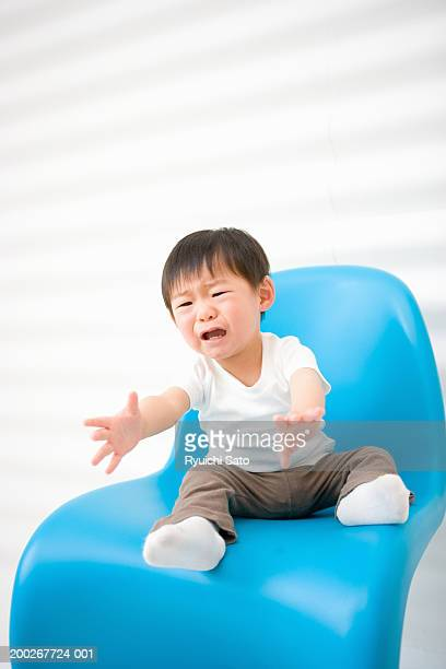 Baby boy (18-21 months) crying on chair, arms outstretched