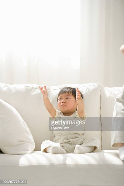 Baby boy (18-21 months) crying on sofa, arms outstretched