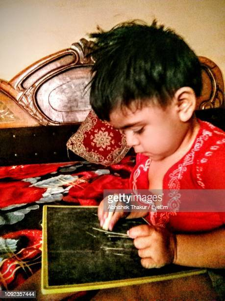 Baby Boy Drawing On Blackboard At Home