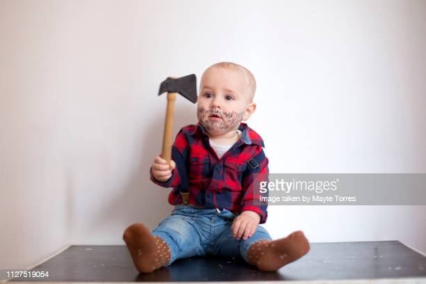 Baby boy dressed as a woodcutter and sitting down