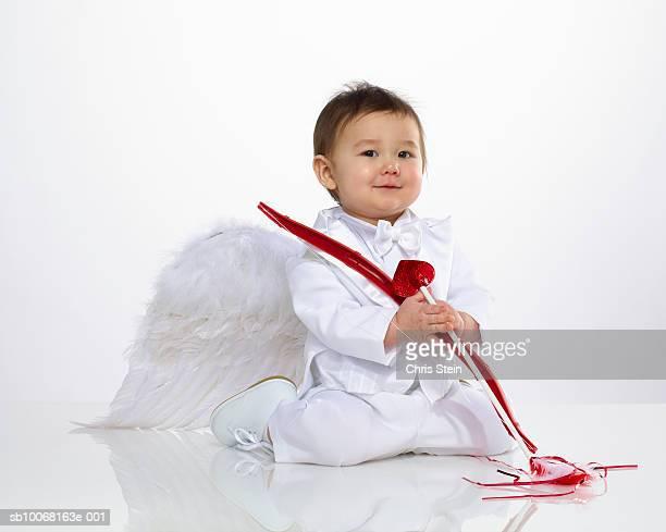 Baby boy (6-11 months) dressed as cupid, studio portrait