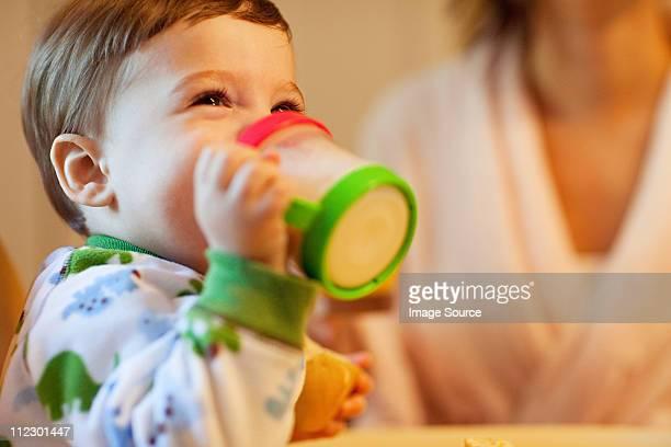 Baby boy drinking from beaker