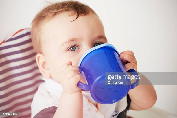 Baby boy drinking in baby chair