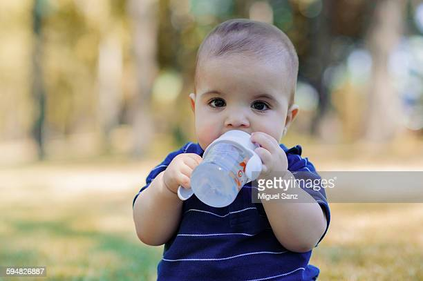 Baby boy drinking milk from his bottle