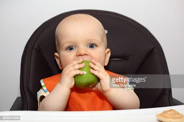 Baby boy eating an apple