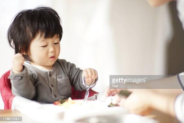 bébé mangeant à la maison - accompagnement photos et images de collection