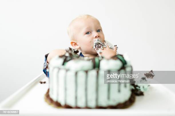Baby boy (12-17 months) eating birthday cake