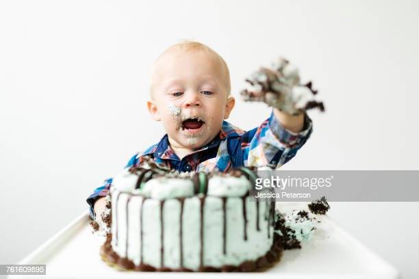 Baby boy (12-17 months) eating birthday cake