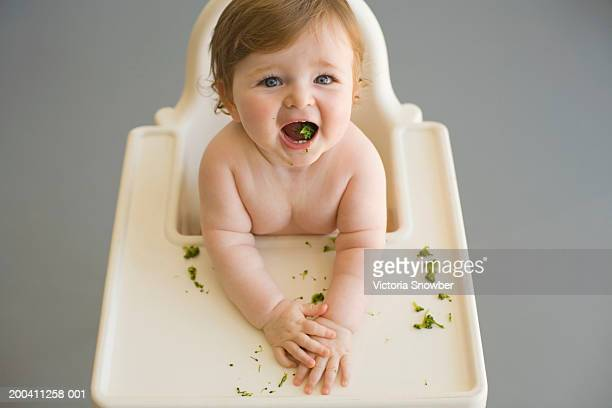 Baby boy (9-12 months) eating broccoli in high chair