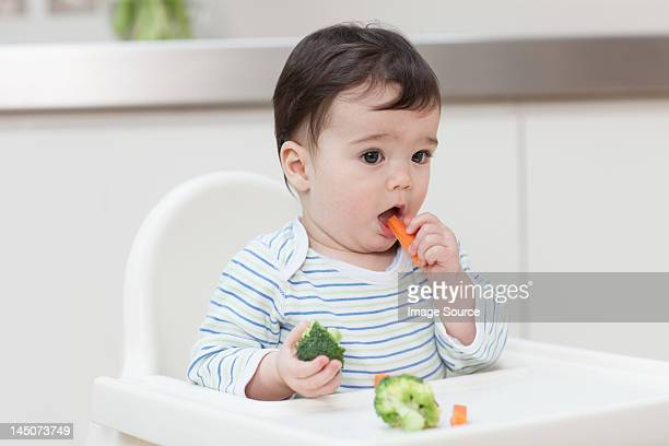 Baby boy eating healthy vegetables