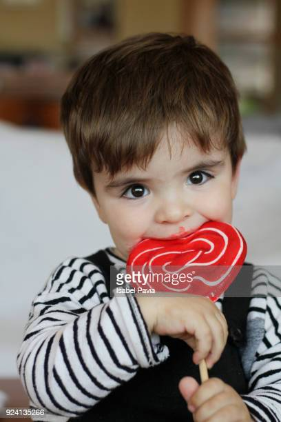 baby boy eating lollipop, portrait - sugar baby imagens e fotografias de stock