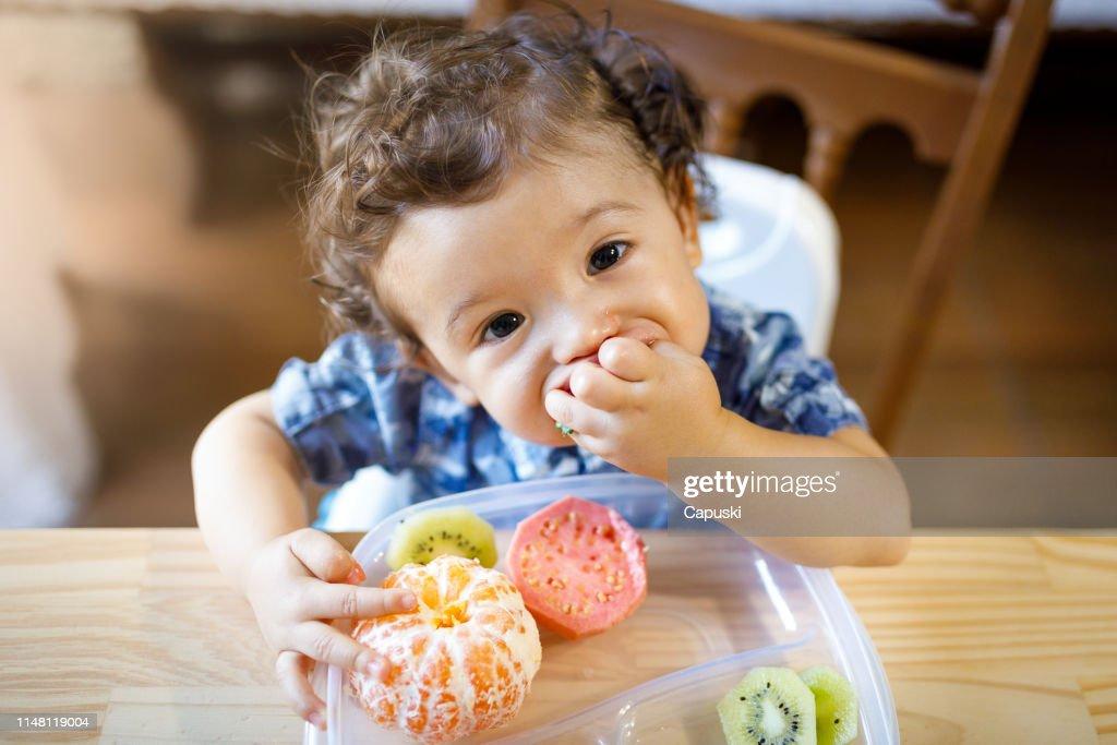 Baby boy eating tasty fruit : Stock Photo