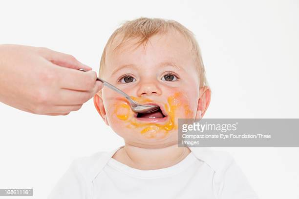 Baby boy eating with food all over face