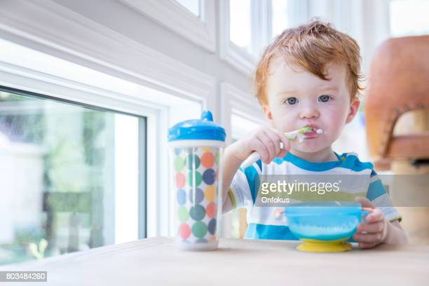 Baby Boy Eating Yogurt Alone with Spoon