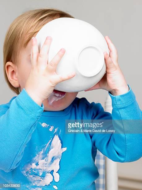 Baby boy eating yogurt, yogurt all over his tshirt