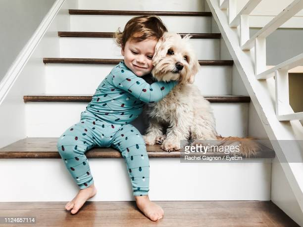 baby boy embracing dog on steps in forest - pets stock pictures, royalty-free photos & images