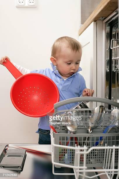 Baby boy emptying a dishwasher