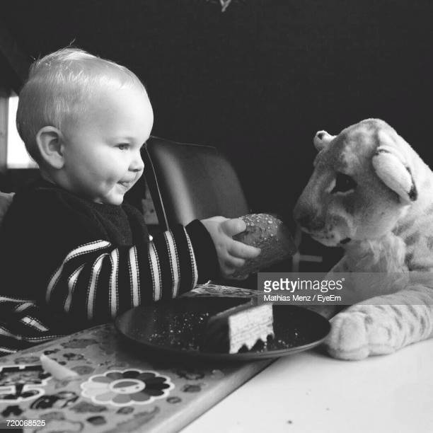 Baby Boy Feeding Bun To Toy Lion Cub On Dining Table At Home