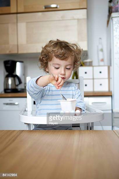 Baby boy feeding himself yoghurt