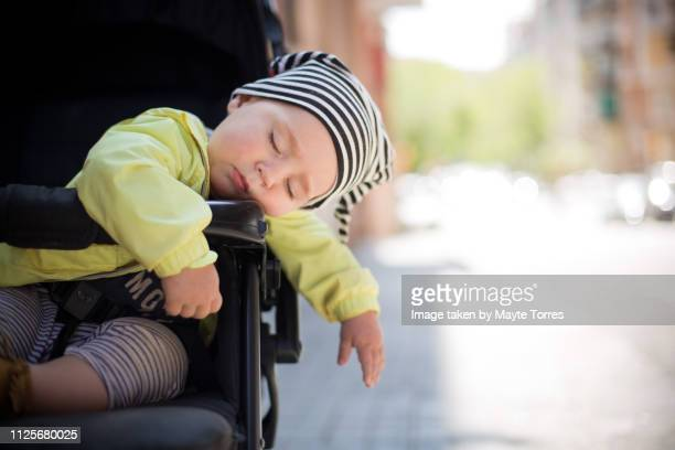 baby boy fell asleep on the stroller - baby stroller stock pictures, royalty-free photos & images