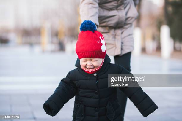 baby boy firsts steps in the winter - winter coat stock pictures, royalty-free photos & images