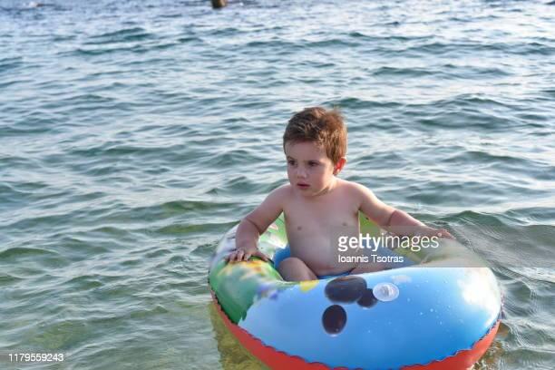 baby boy floating in ocean in inflatable raft - messenia fotografías e imágenes de stock