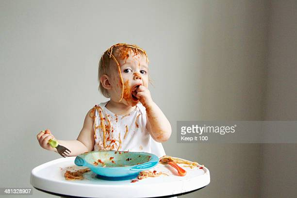 Baby boy getting messy eating spaghetti