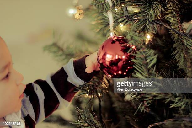 Baby boy grabbing red ball christmas ornament