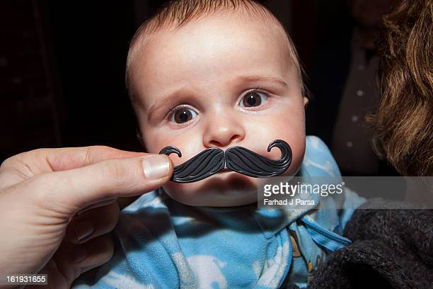 Baby boy has fake curly mustache held up to him.