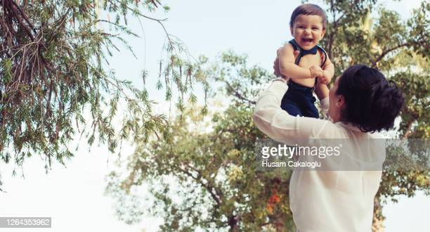 baby boy having a happy time playing with her in her mother's lap. - women in suspenders stock pictures, royalty-free photos & images