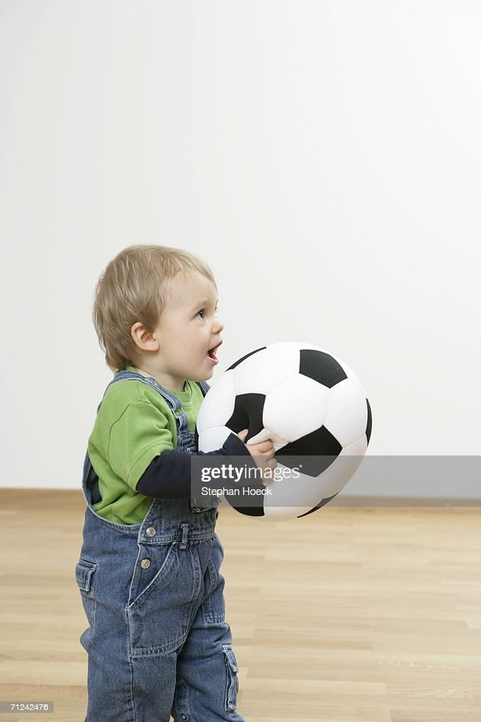 Baby boy holding a football : Stock Photo