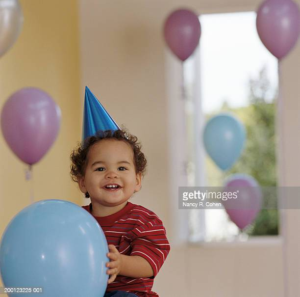 Baby boy (12-15 months) holding balloon, wearing party hat, portrait