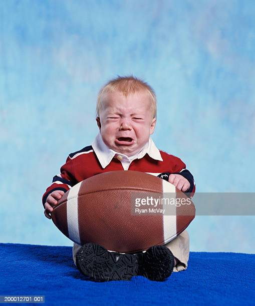 Baby boy (3-6 months) holding football, crying, portrait