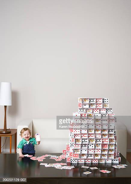 baby boy (9-12 months) holding playing card box beside house of cards - wonderkind stockfoto's en -beelden