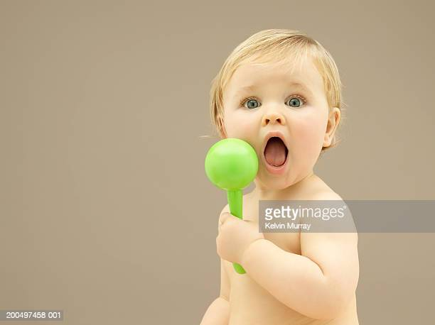 Baby boy (9-12 months) holding rattle, mouth open, close-up, portrait