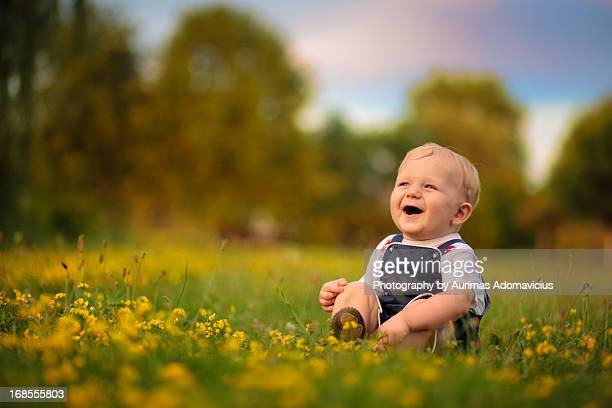 Baby boy in a field, laughing