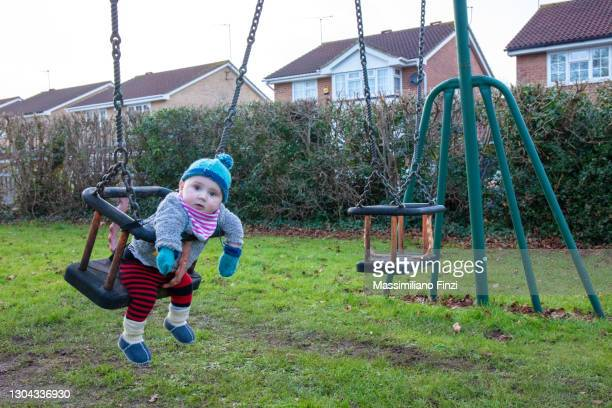 baby boy in a swing outdoor.  having fun outdoor. happy family concept - one baby boy only stock pictures, royalty-free photos & images