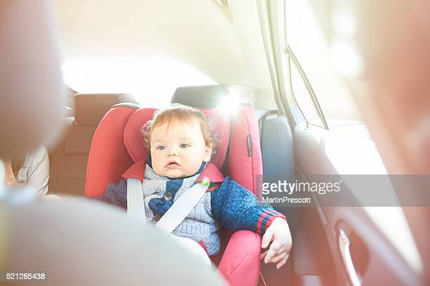 Baby boy in car seat watching DVD