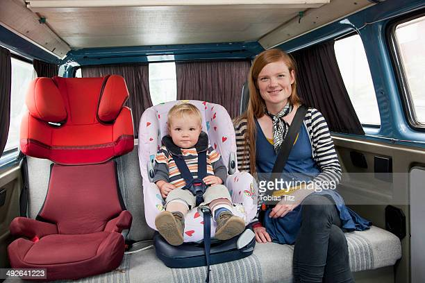 Baby boy in car seat with mother in back seat